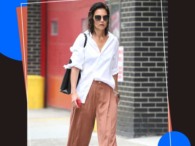 Katie Holmes in NYC wearing a white button down shirt with brown pleated pants and Gucci loafers.