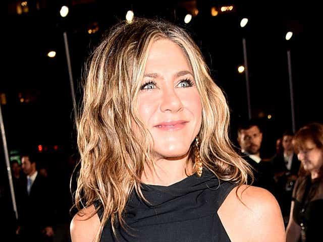 Jennifer Aniston smiling in a black dress.