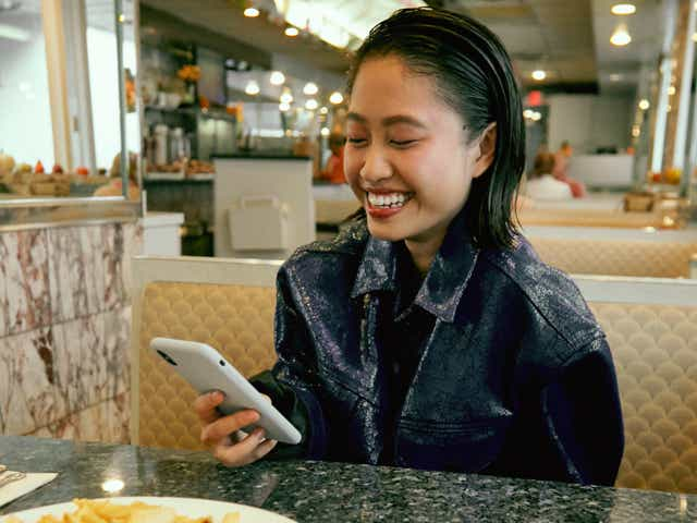 A person sitting in a restaurant booth in front of a plate of french fries, holding their phone in their hand and smiling while looking at their phone screen.
