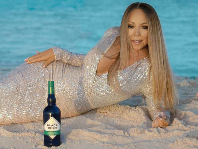 Mariah Carey in sequin gown on the beach with a bottle of liquor in front of her.