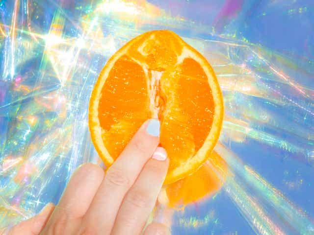 Doigts touchant une orange faisant allusion à la masturbation