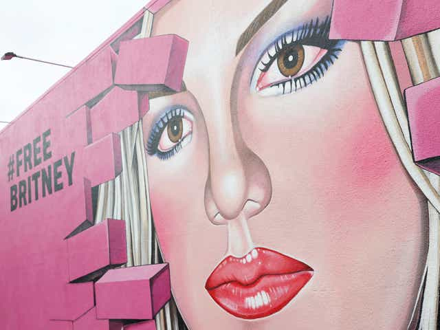A wall mural of a woman's (Britney Spears) face next to text reading #FreeBritney