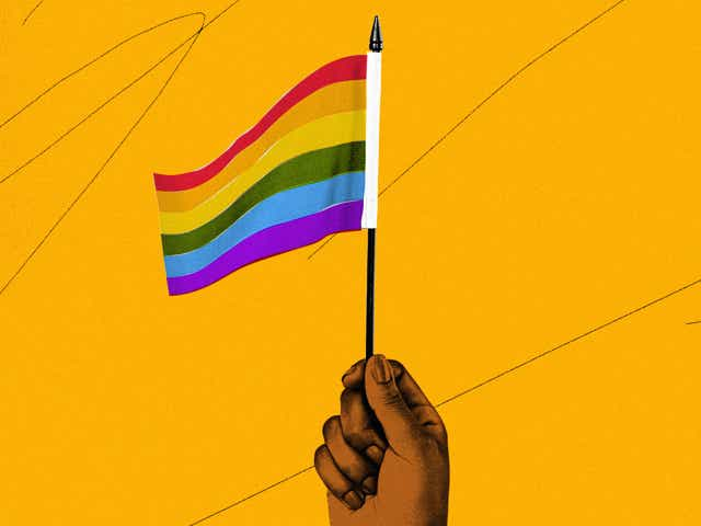 An illustration of a hand holding a Pride flag on a yellow background