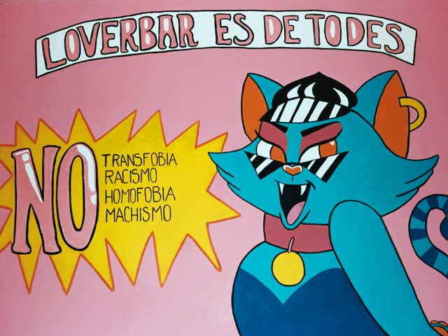 """Photography of a sign that reads """"Loverbar es de todes, no transfobia, no racismo, no homofobia, no machismo"""" with a drawing of a cat smiling next to it."""