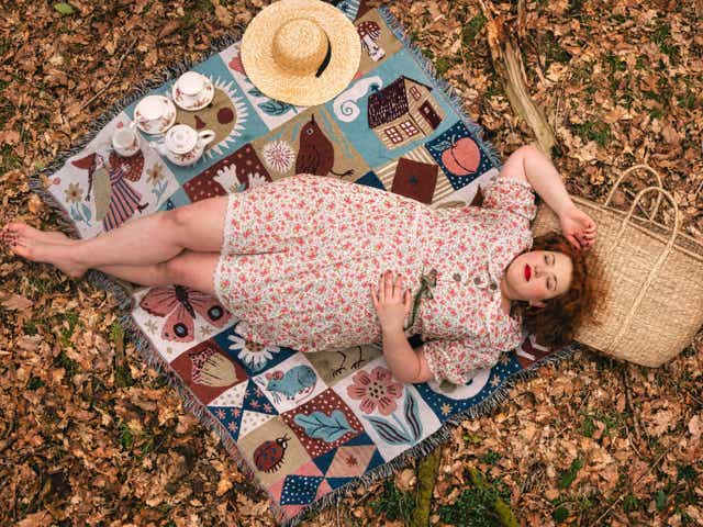 Image of Marie Southard Ospina lying on a picnic blanket photographed from above wearing a floral patterned dress