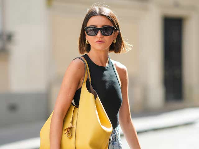 PARIS, FRANCE - AUGUST 27: Alexandra Pereira wears black sunglasses, gold earrings, a black ribbed halter-neck cropped t-shirt, blue faded denim high waist ripped flared jeans pants, a large yellow shiny leather shoulder bag from Tods, silver rings, on August 27, 2021 in Paris, France. (Photo by Edward Berthelot/Getty Images)
