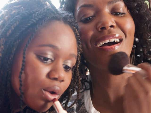 Black mother and daughter putting on makeup