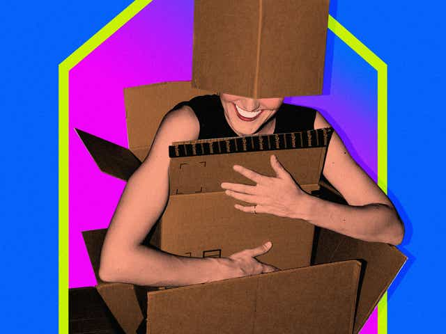 A woman holding a bunch of boxes