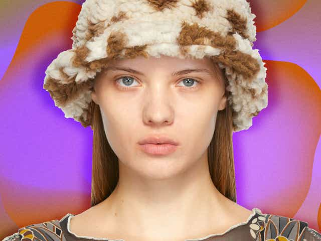 A woman in a fuzzy bucket hat on a purple and orange background