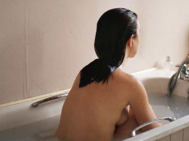 Person sitting in bath, facing away from the camera.
