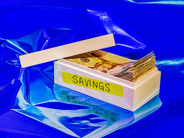 """A box with a label on the outside reading """"savings"""", the lid open to show it's filled with cash."""