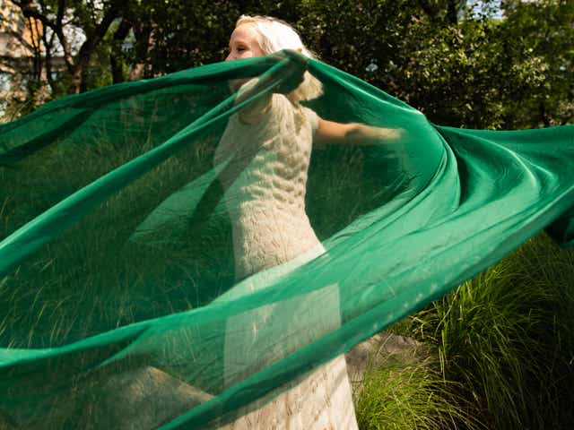 A woman spinning in a circle, her green silk scarf swept up in the swirling air