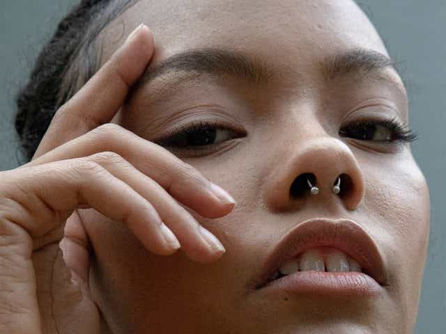 Model photographed up close with her hand placed on her face framing the eye area
