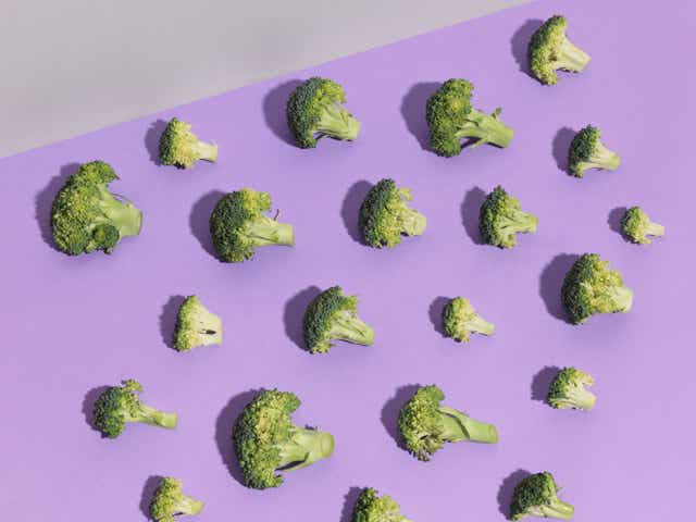 Broccoli pieces on a purple background.