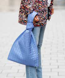 A street-style model wears light-wash jeans, a multicolored jacket, and carries a lavender quilted purse.