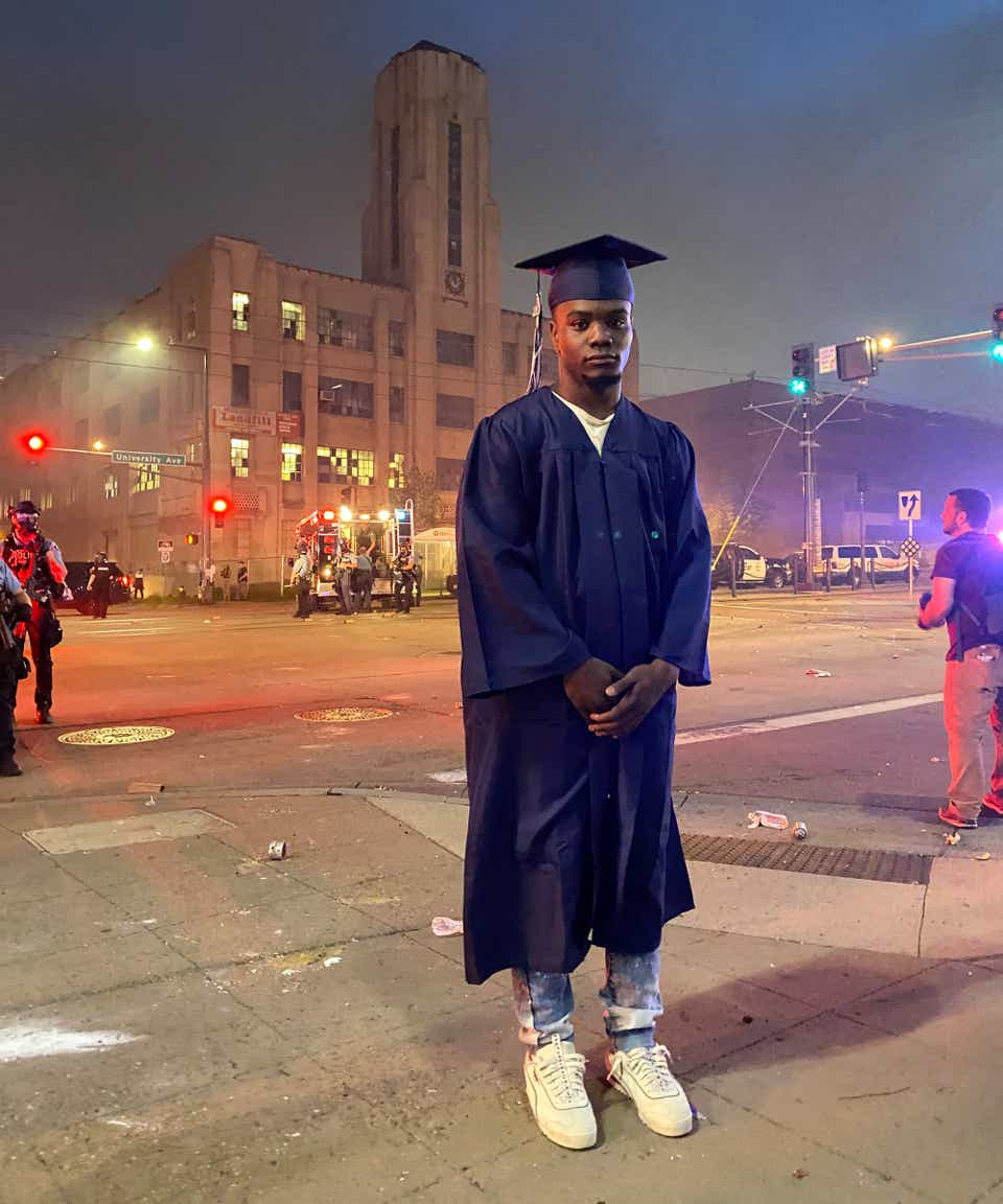 A young Black man in a graduation cap and gown, standing in front of a building with flashing lights, cops, and reporters, in the background.