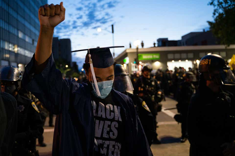 An image of a young Black man in a graduation cap and gown, also wearing a medical mask, with his fist raised.