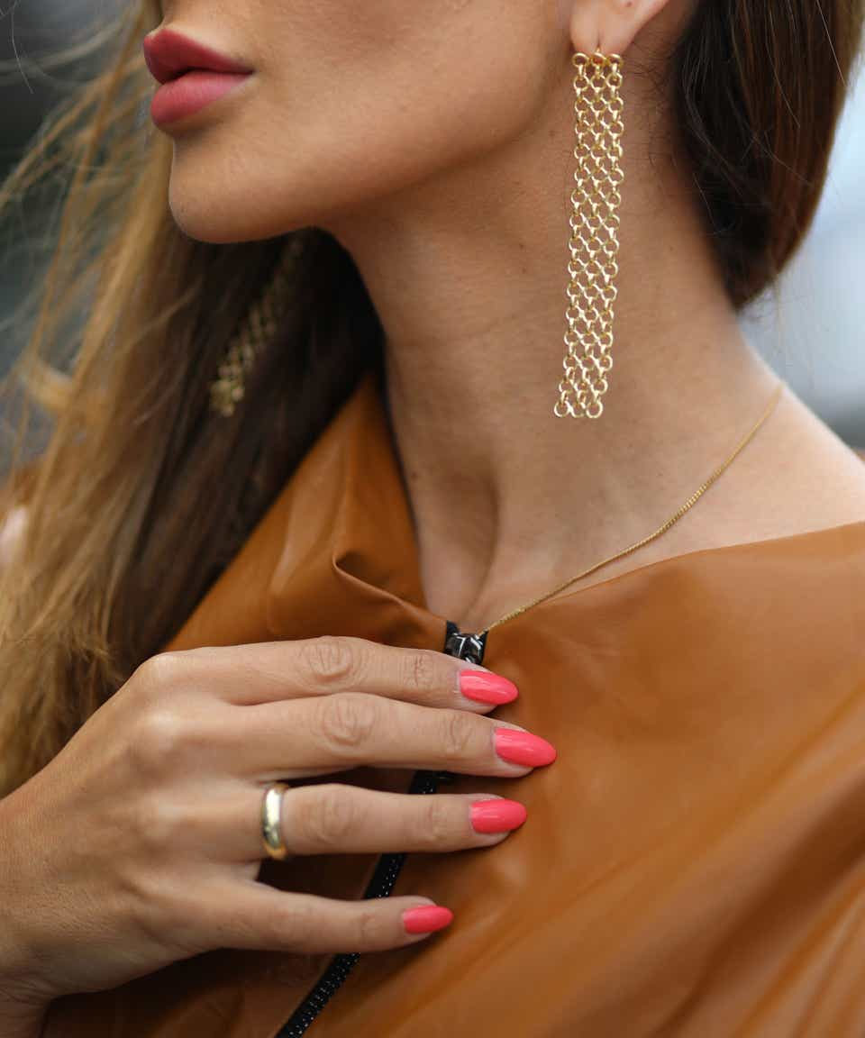 A street-style model wears a brown leather top, gold dangly earrings, and a bright coral manicure.