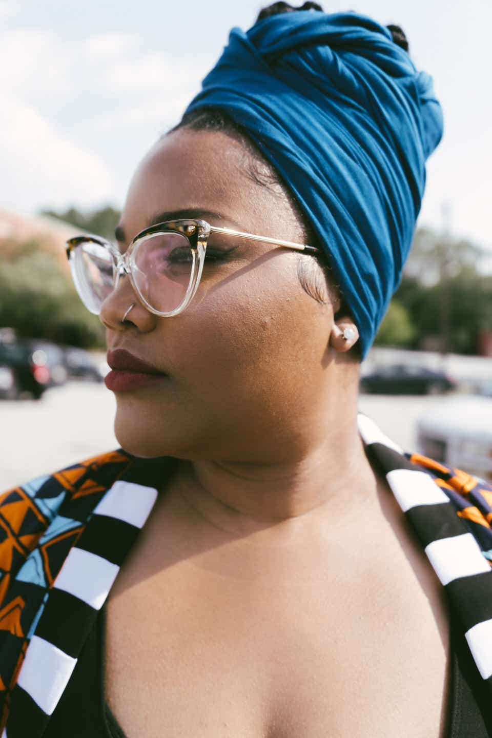 This is a close up shot of Erica's silhouette. She is wearing a blue headwrap, oversized cat-eye glasses, and a cardigan patterned with geometric shapes.