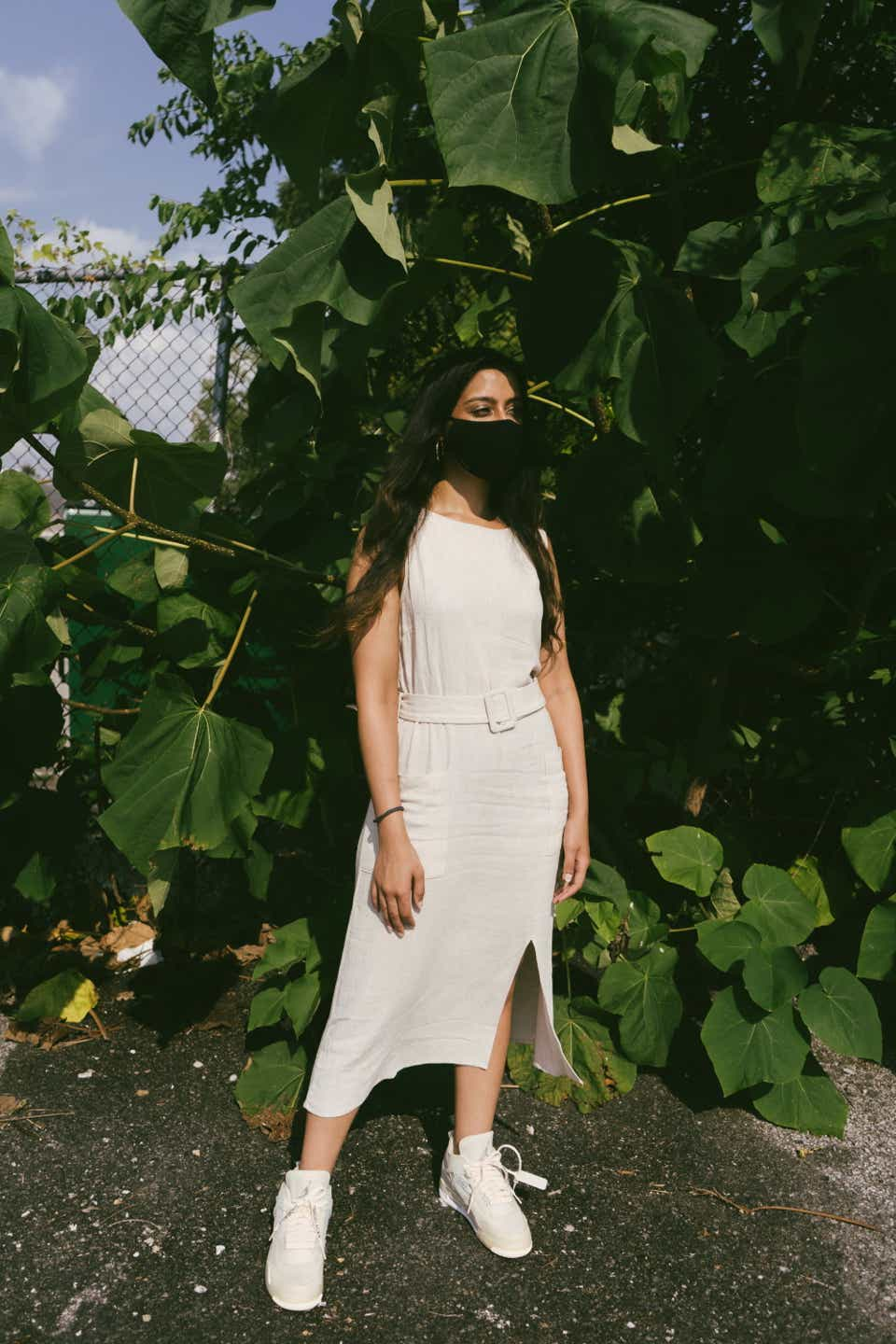 Kashish is wearing a black mask with a cream-colored linen, belted dress with a slit. For footwear, she's wearing high-top Off-White x Nike/Jordan sneakers.