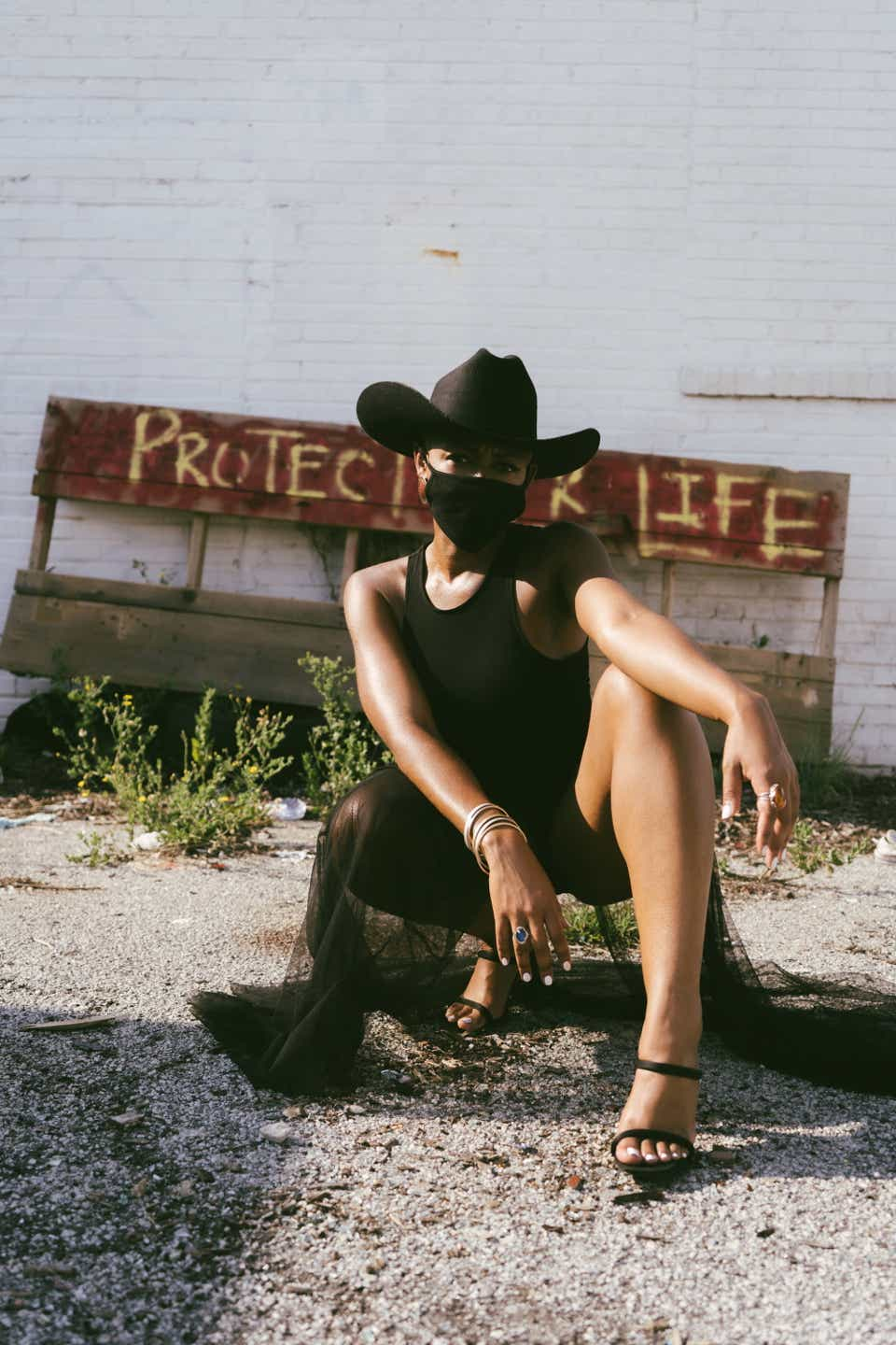 Jasmine is posing on the ground, showing off her black strappy sandals. She is wearing a black cowboy hat, a black mask, and a black dress.