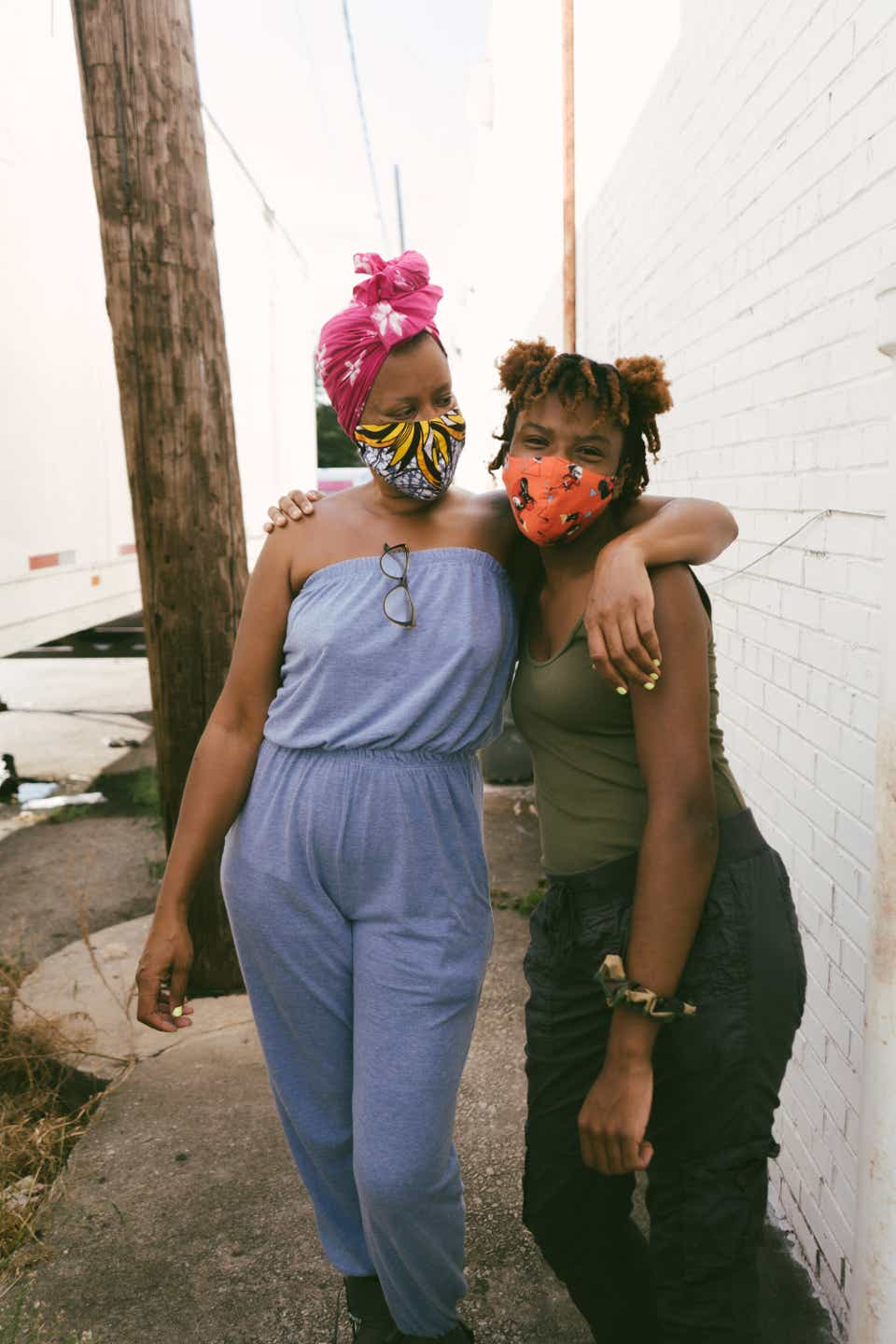 This is a photo of two sisters, one with the arm around the other. Meredith (on the left) is wearing a pink headscarf with a yellow, patterned face mask, and a light blue, strapless jumpsuit. Her sister Brooklyn is wearing her hair in space buns, and has on an orange face mask, a forest green tank top, and black pants.