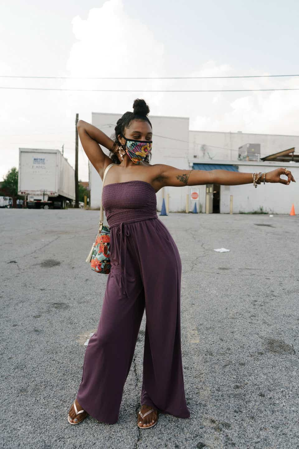 Jazmin is posing with one arm sretched out while wearing a colorful, patterned face mask and a dark purple, strapless jumpsuit. She is carrying an orange drawstring purse and wearing simple flip flops.