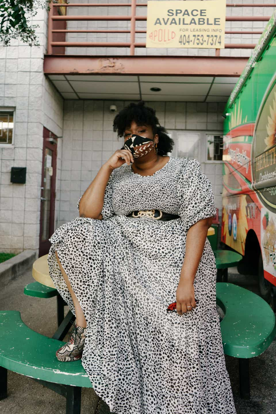Olamma is posing atop a green lunch table in a black-and-white leopard print dress with puff sleeves. She has the dress belted with a black belt and is wearing a black-and-brown face mask.
