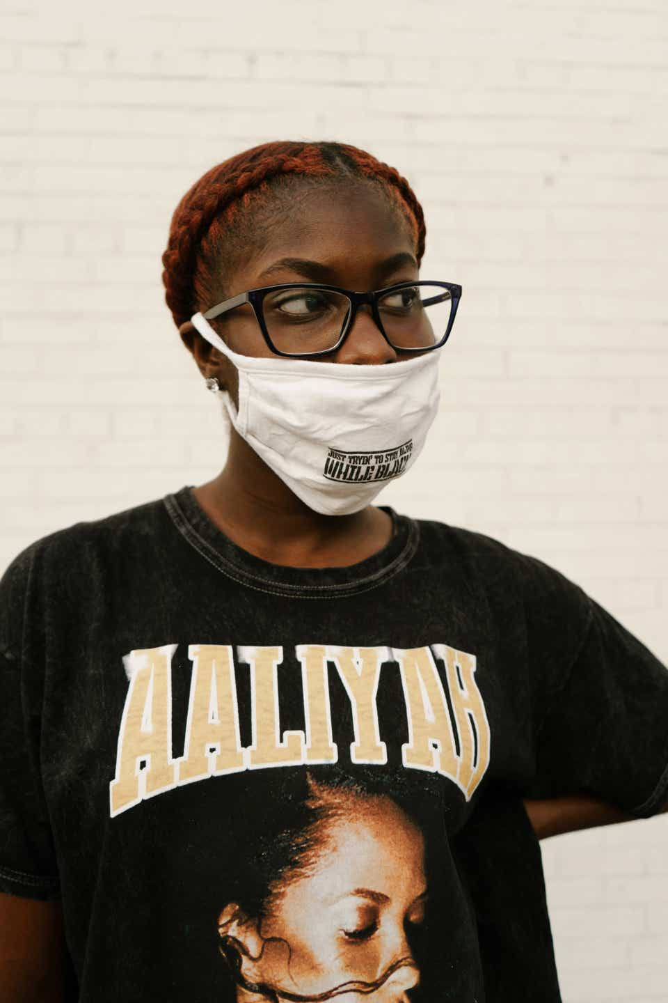 """Jewelle is looking to the side while wearing black-rimmed eyeglasses, a white mask, and a T-shirt that says, """"Aaliyah"""" on it, with a picture of the late singer on the front."""