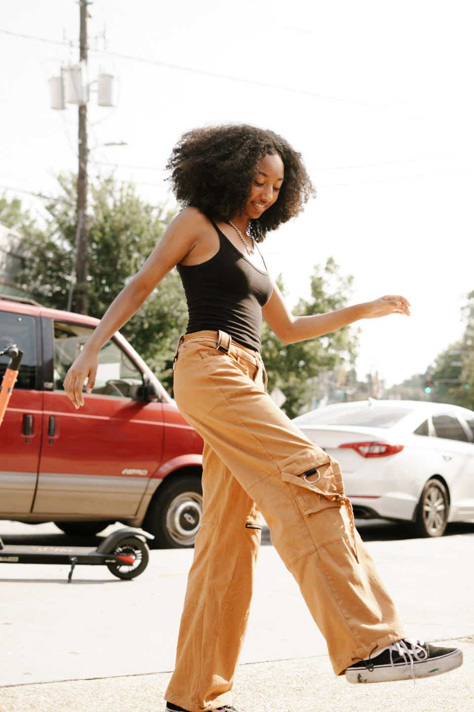 Justyce is dancing while wearing a black tank top, yellow cargo pants, and black Vans sneakers.