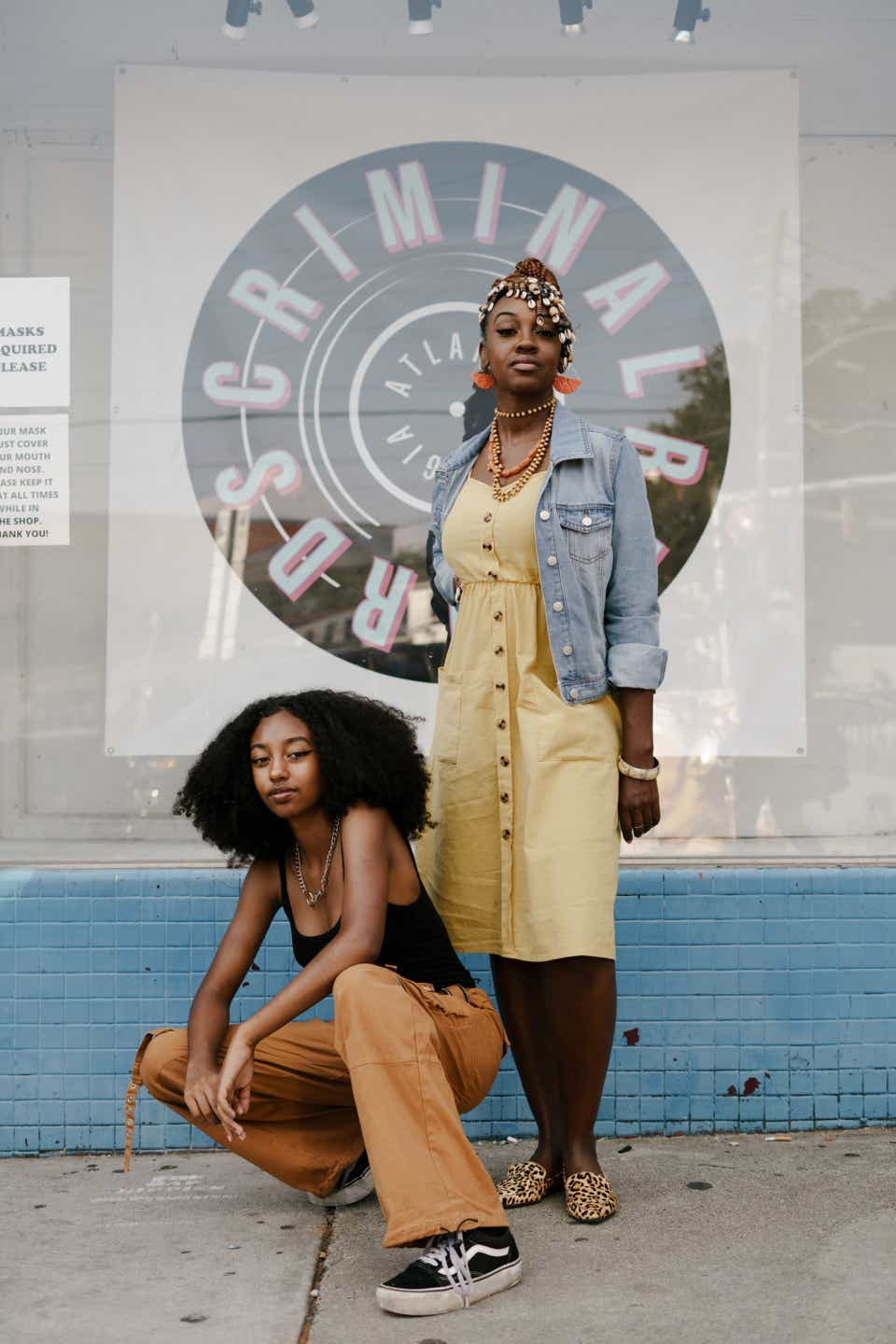 Justyce and Ashley are posing together outside of a local record shop. Justyce is crouching down while wearing a black tank top, orange cargo pants, and Vans sneakers. Ashley is wearing red earrings, a denim jacket, a yellow button-down sundress, and leopard print loafers.
