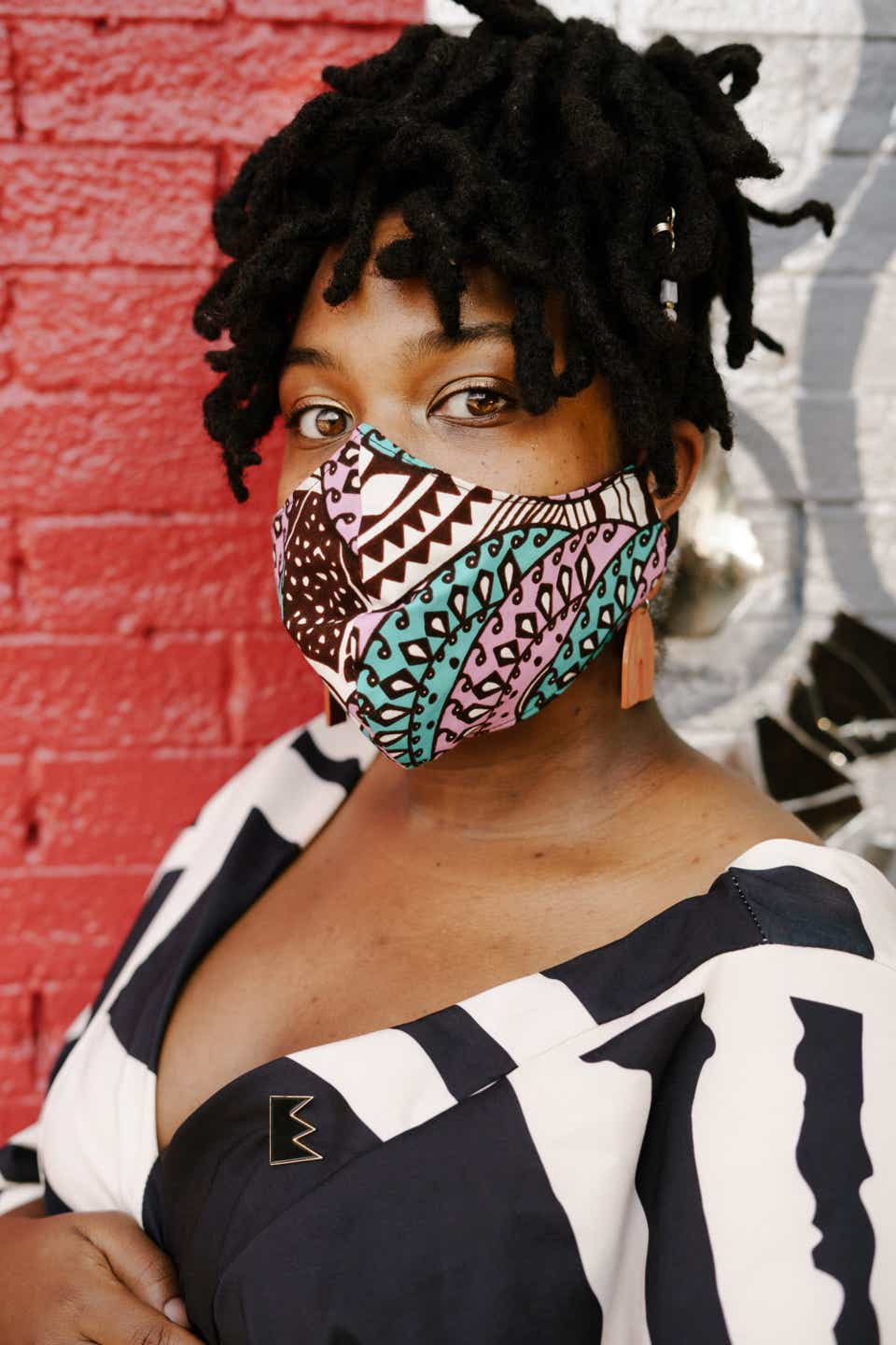 This is an up-close shot of Ayanna, who is wearing a multi-colored, geometric-patterned face mask, with orange earrings, and a black-and-white dress.
