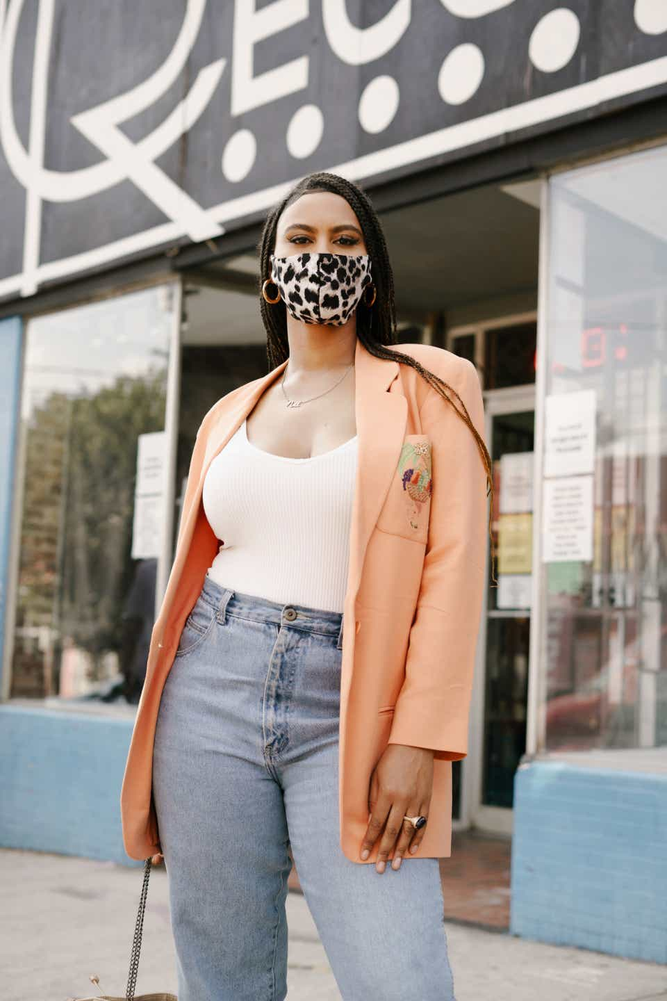 Janai is wearing a leopard print face mask, which she paired with a white tank top, a peach-colored blazer, and light-wash jeans.