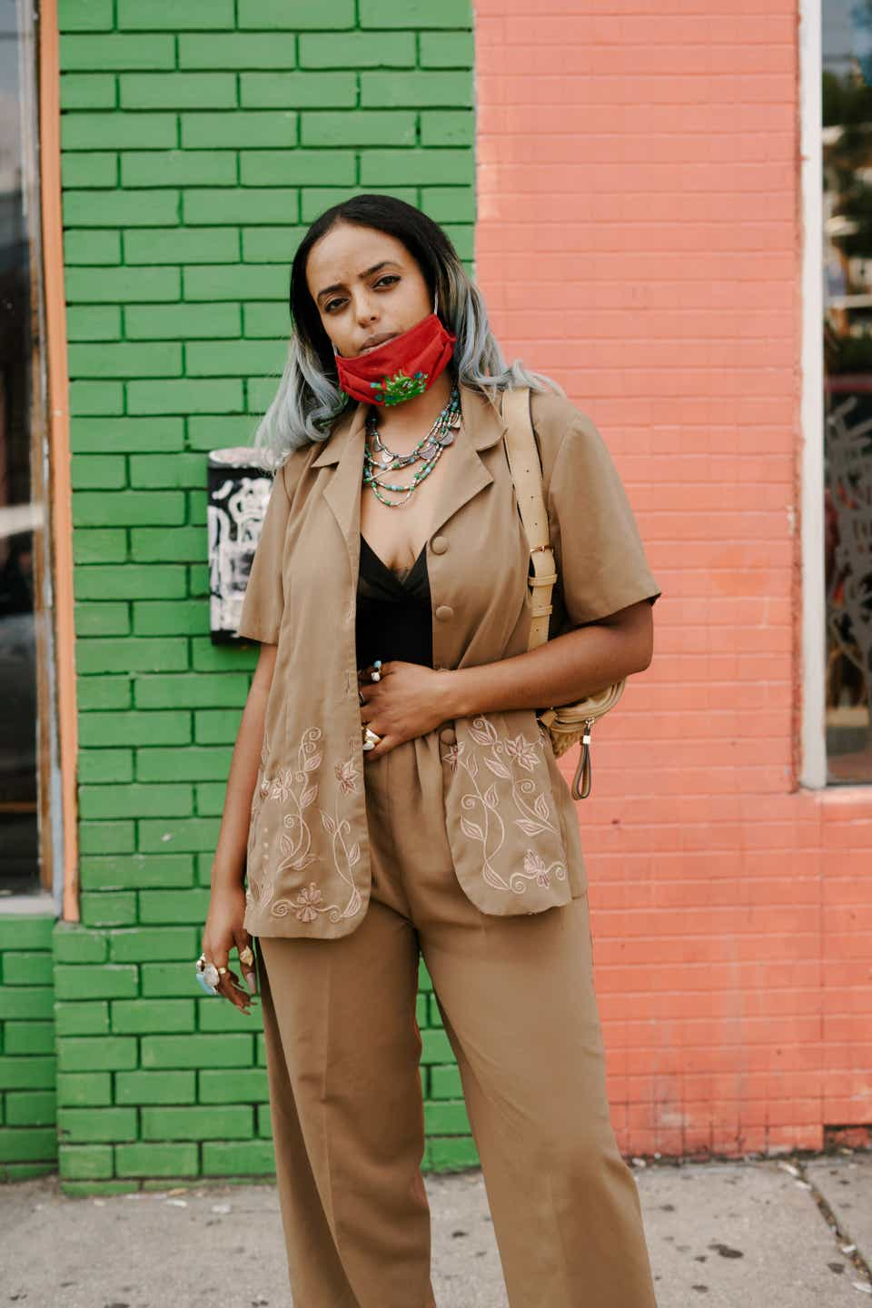 Devora is wearing a red mask and showing off her dyed silver hair. She has on a camel-colored suit with short sleeves, and a black tank top underneath.
