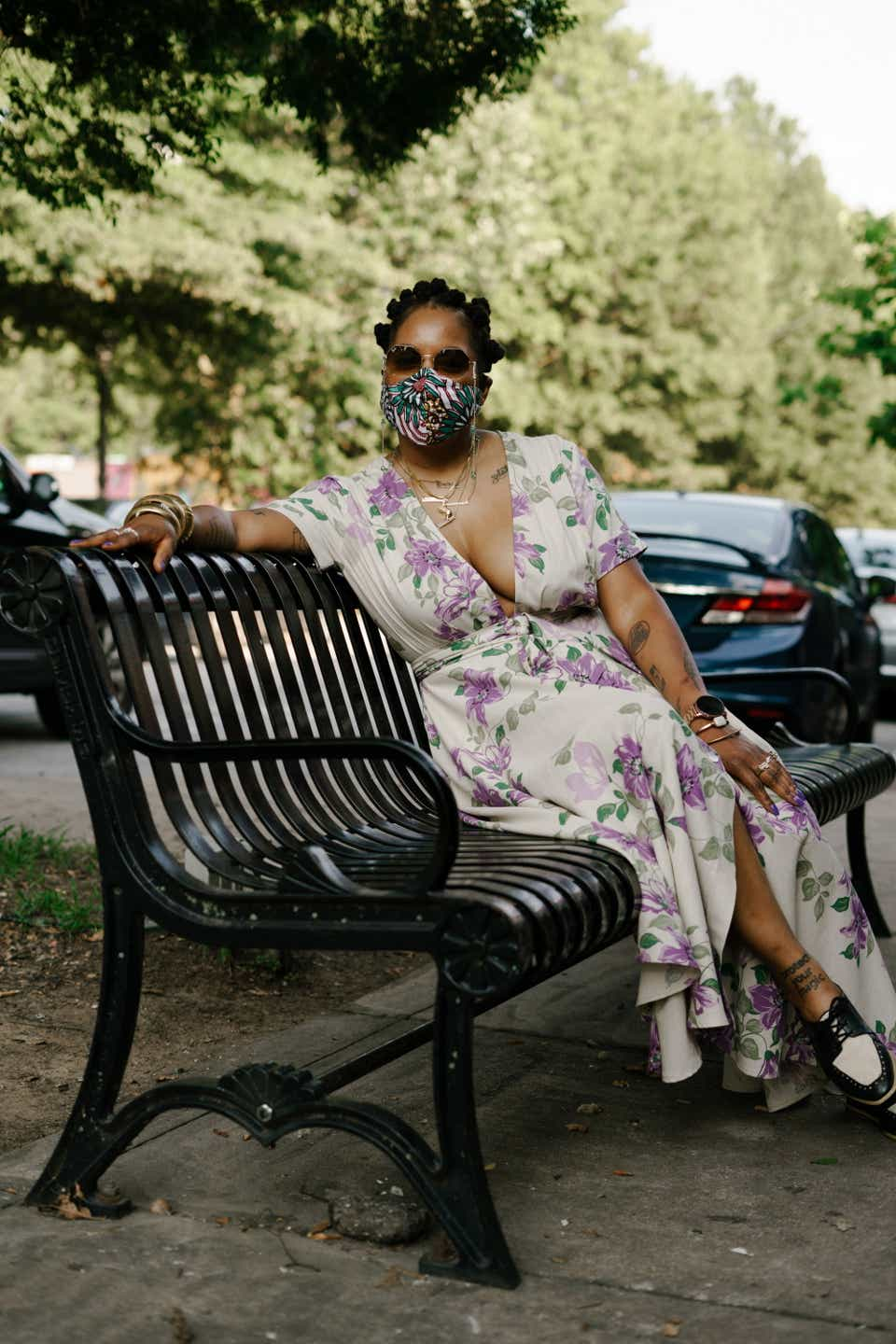 Kwajelyn is sitting on a park bench wearing a cream-colored, V-neck sundress with purple flowers on it. Her mask is patterned with geometric shapes and her shoes are black-and-white loafers.