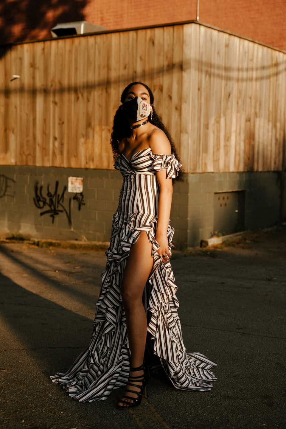 Layla is wearing an off-the-shoulder striped maxi dress with a high-slit and a ruffled train. She has on lace-up black sandals and a face mask.