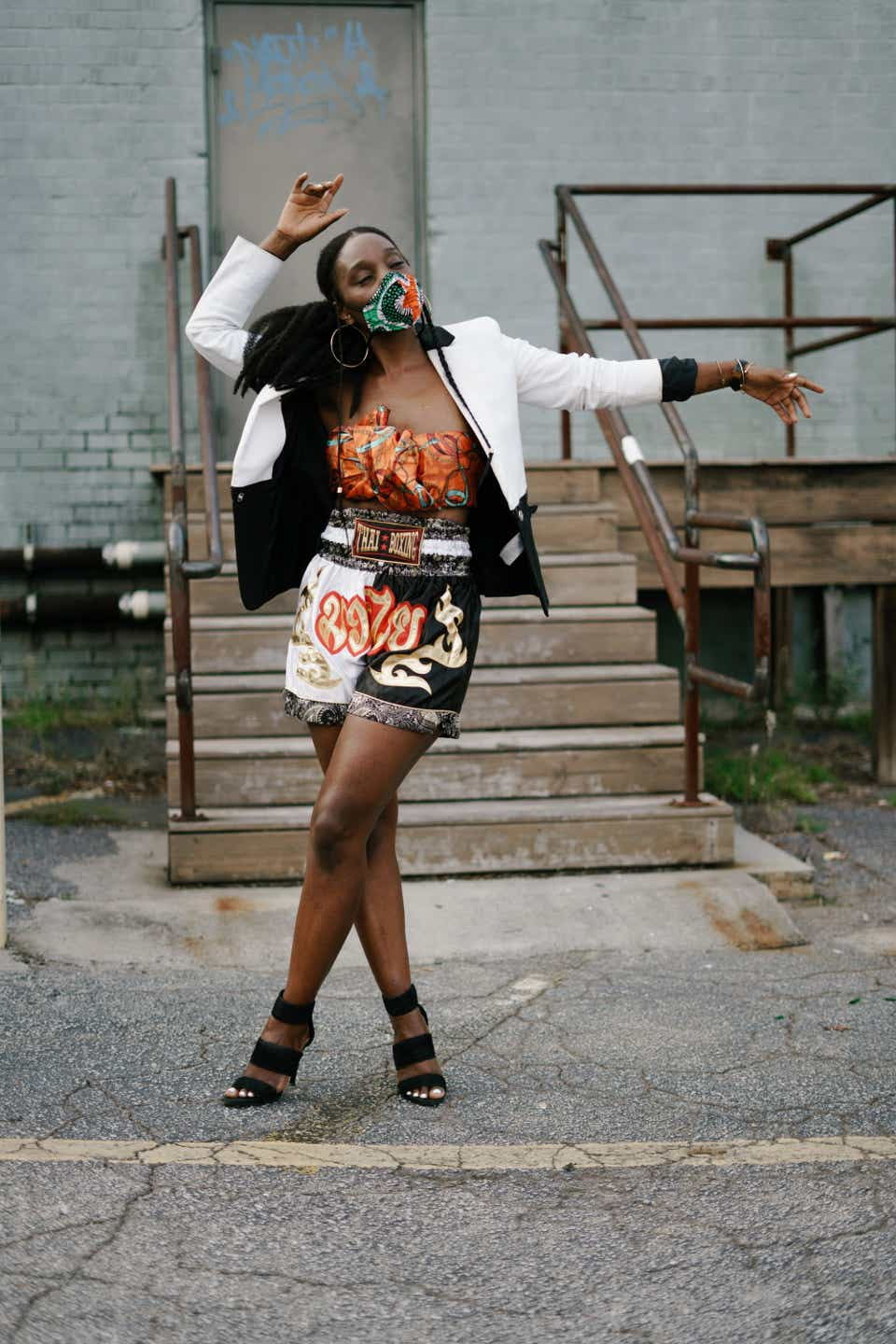 Naira is dancing while wearing a patterned orange tube top with Muay Thai boxing shorts and a black-and-white collared jacket. Her mask is green and orange, and she has gold hoop earrings and black sandals on.