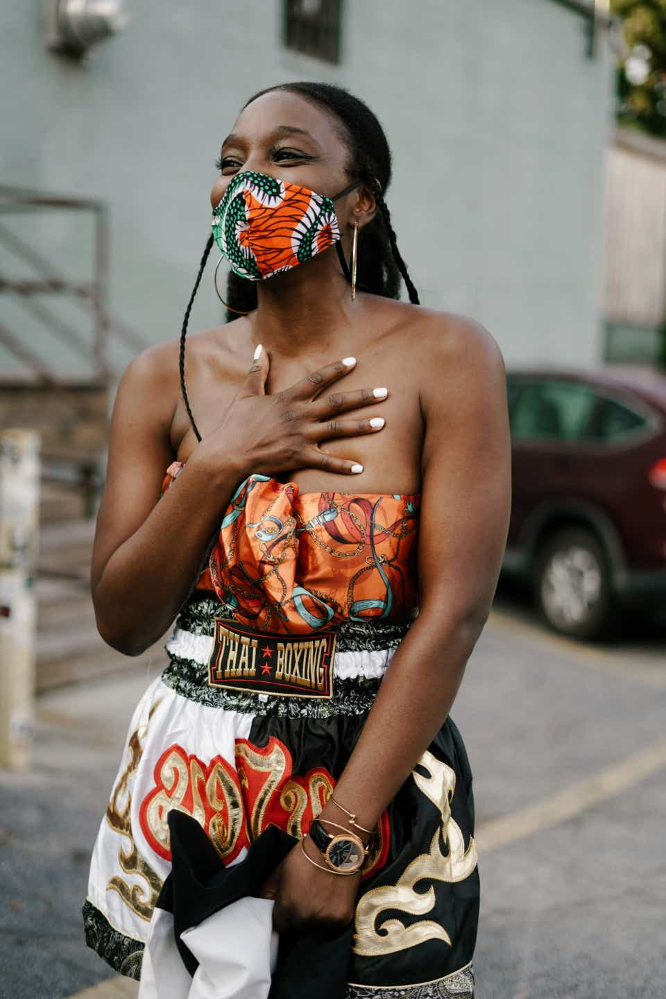 Naira is wearing a patterned orange tube top with Muay Thai boxing shorts. Her mask is green and orange, and she has gold hoop earrings on.