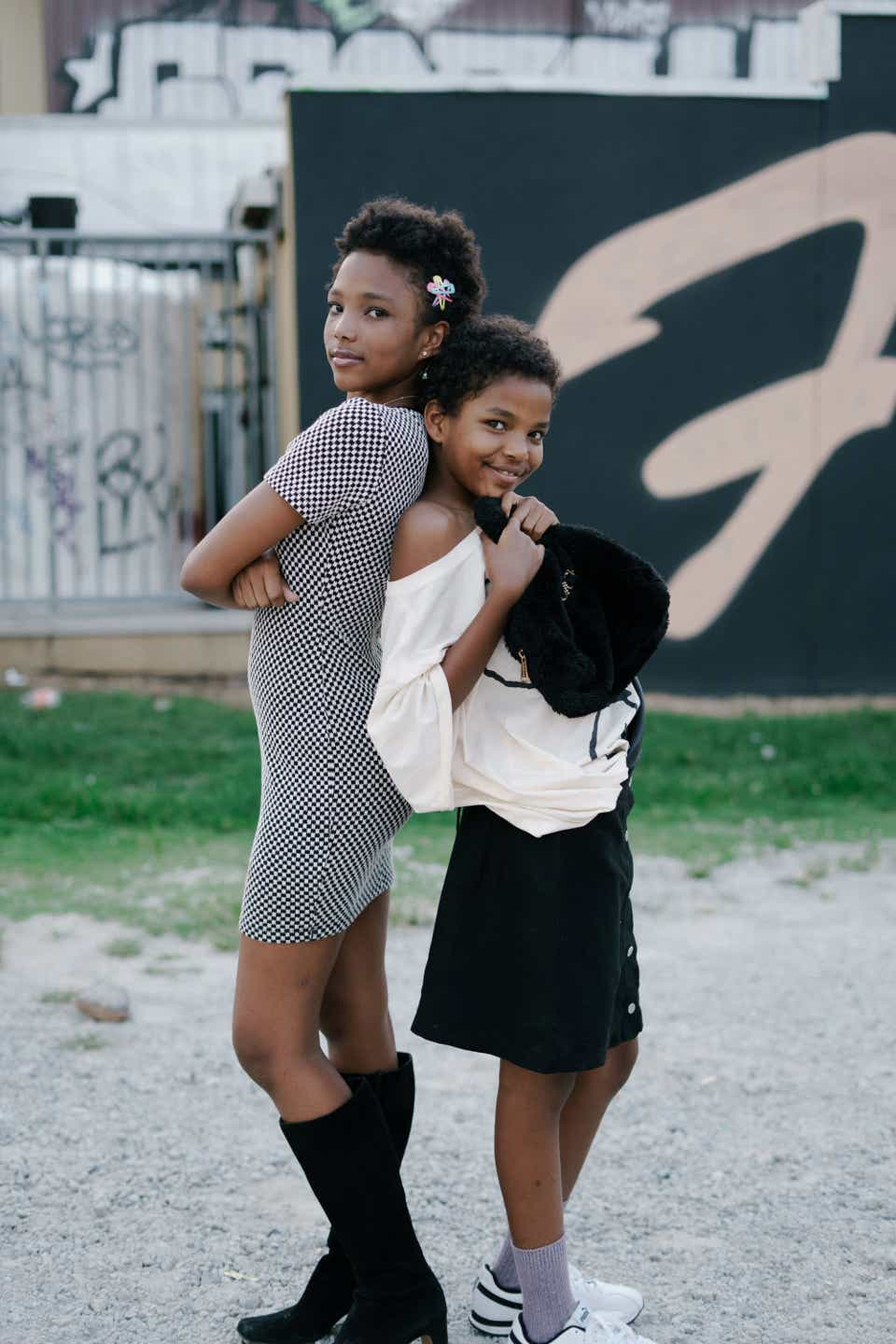 Sisters Aélaa & Jahara Bell are seen posing with their backs to each other. Aélaa on the left is older and picked out a black-and-white short-sleeved mini dress and paired it with knee-high black go go boots. Her little sister Jahara is wearing a white, oversized T-shirt with a black purse and a black mini skirt. She's also wearing gray socks and white sneakers.