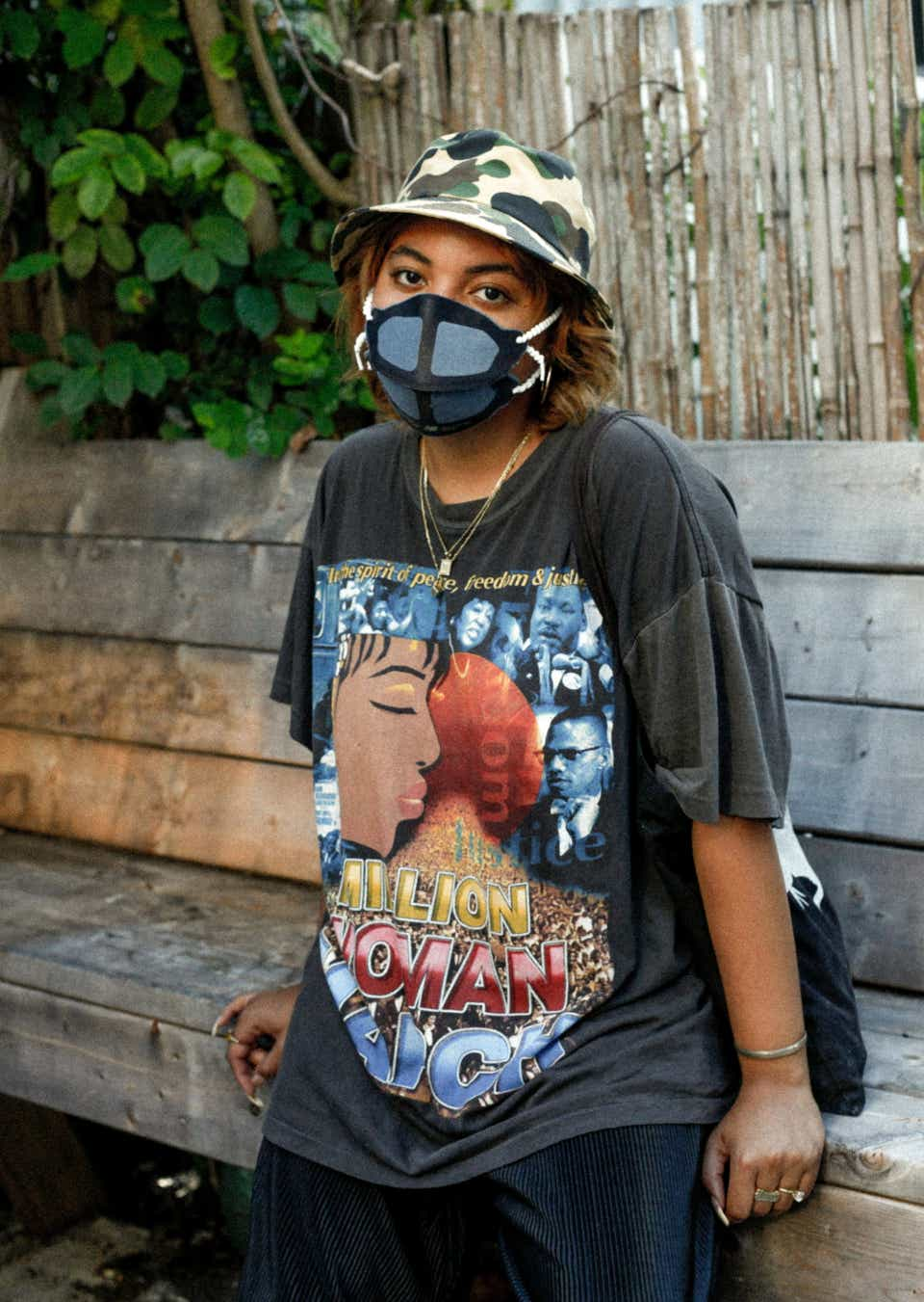 Rudi is wearing a camo-print bucket hat, a denim-and-black face mask, and a black, vintage T-shirt for the Women's March.