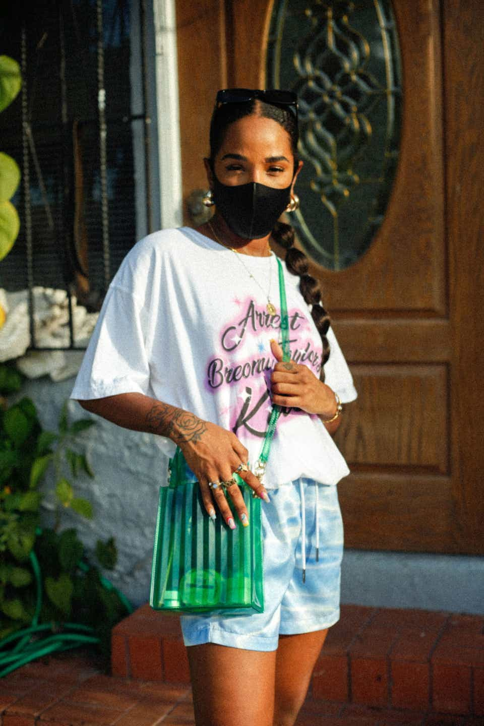 """Dani Jane wears an oversized white t-shirt with the words """"Arrest the cops that killed Breonna Taylor"""" on it with a green bag, Kith shorts, and a black mask."""