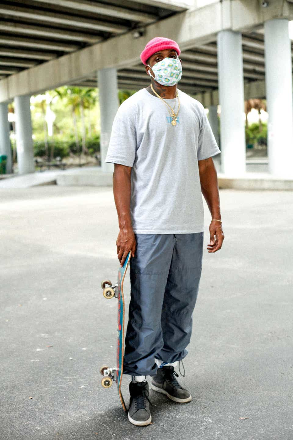James is wearing a white graphic T-shirt, a pink beanie, gray track pants, and gray sneakers. He's wearing a surgical mask and has his skateboard by his side.