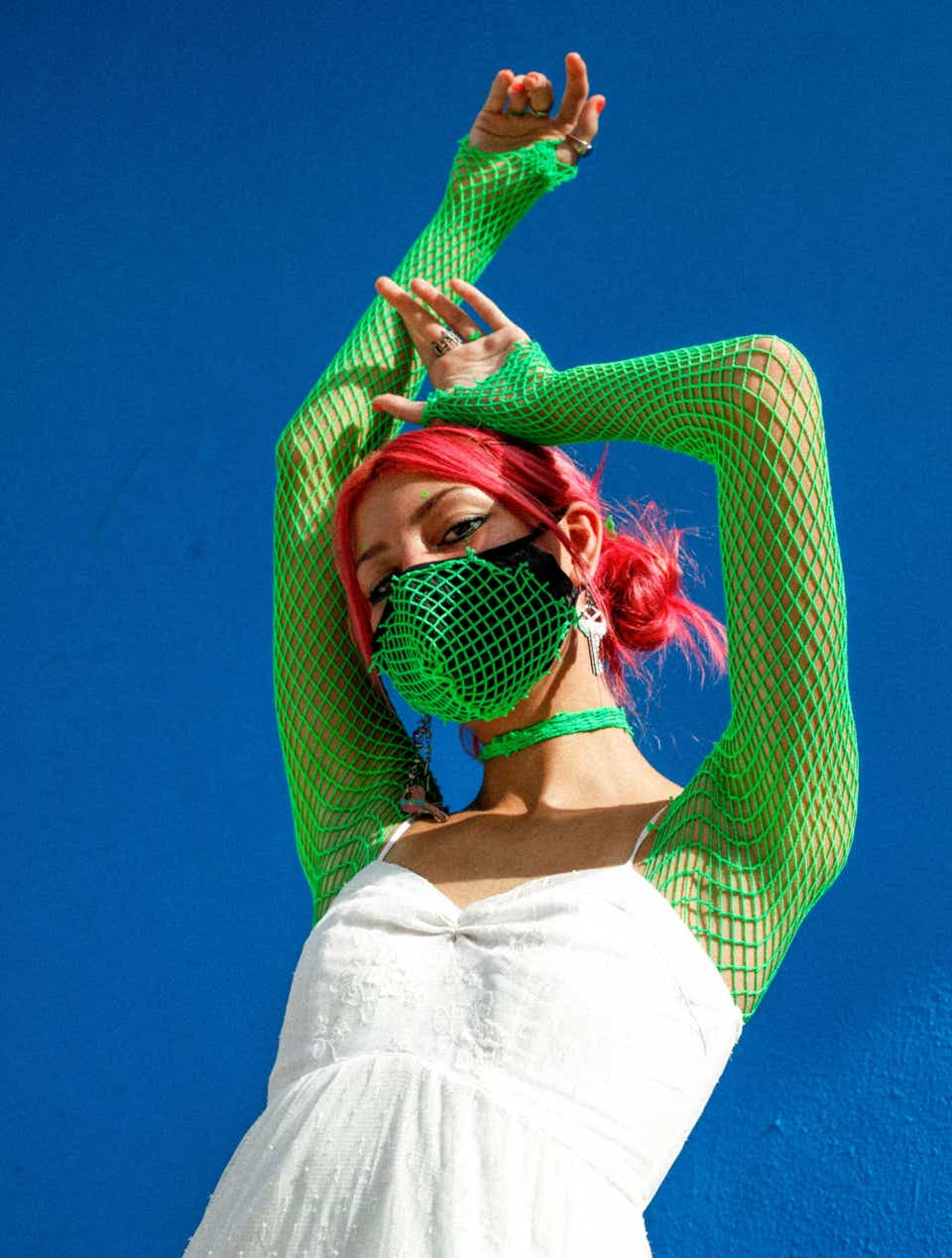 Paris has bright pink hair and is wearing neon green fishnet sleeves with a matching face mask. Layered on top of her fishnet sleeves is a little white dress.