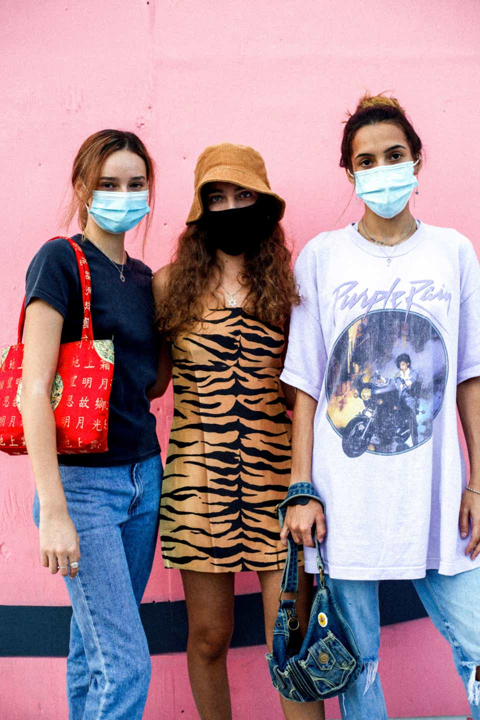 Three friends pose against a pink wall. The person on the left, Anarella, wears a black T-shirt, blue jeans, and a red handbag. The middle person, Dania, is wearing a tiger-print mini dress from Realisation Par with an orange bucket hat, and a black mask. The person on the right, Duda, is wearing a surgical mask with an oversized Purple Rain T-shirt, jeans, and a denim handbag.