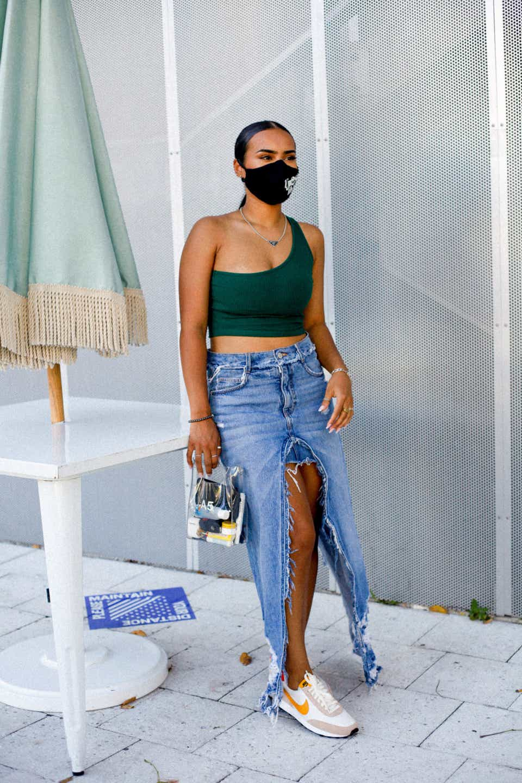 Jessica is wearing a green, one-shoulder top, a Zara denim midi skirt, yellow Nike sneakers, and a transparent Nana Nana A5 handbag. Her mask is black.