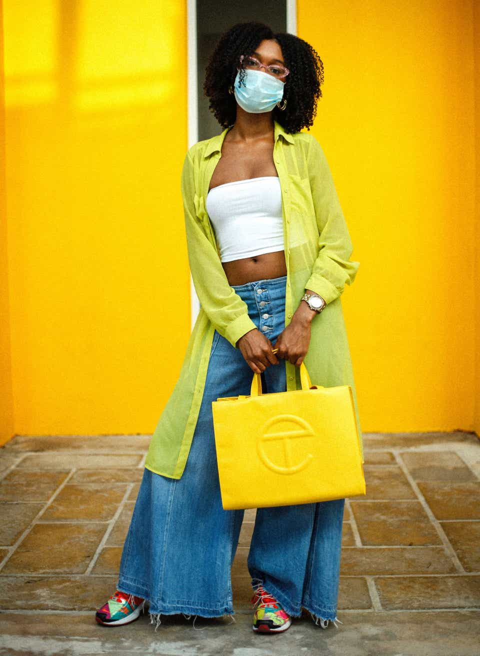Alexandra is wearing a white tube top underneath a neon yellow, sheer button-down. With them, she paired vintage wide-leg jeans with Atmos x Nike Air Max 2 Lights sneakers and a yellow Telfar bag.