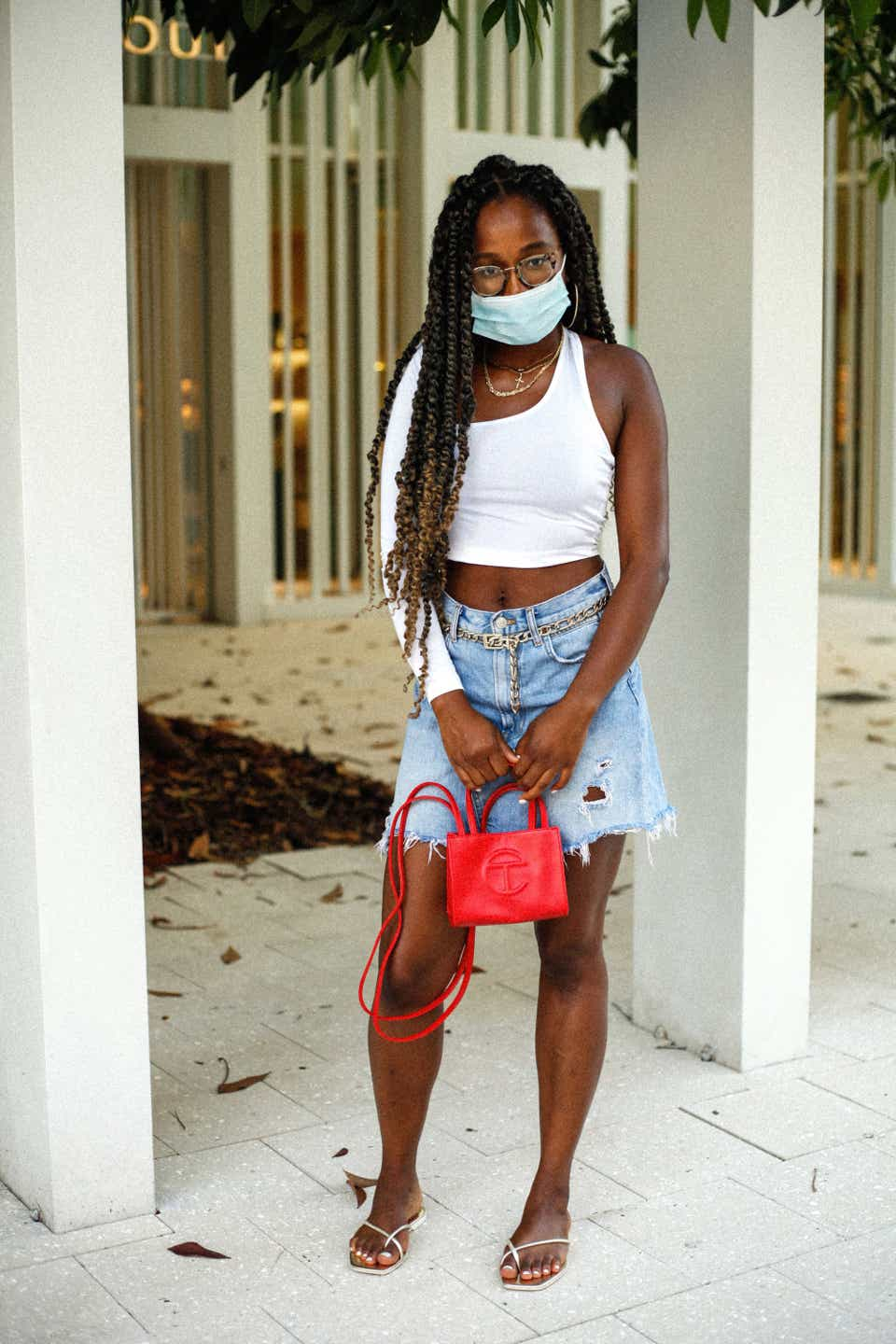 Kristi is wearing a white tank top with asymmetric sleeves, a denim mini skirt paired with a gold chain belt, and gold sandals. She paired the look with a surgical mask and a red Telfar mini bag.