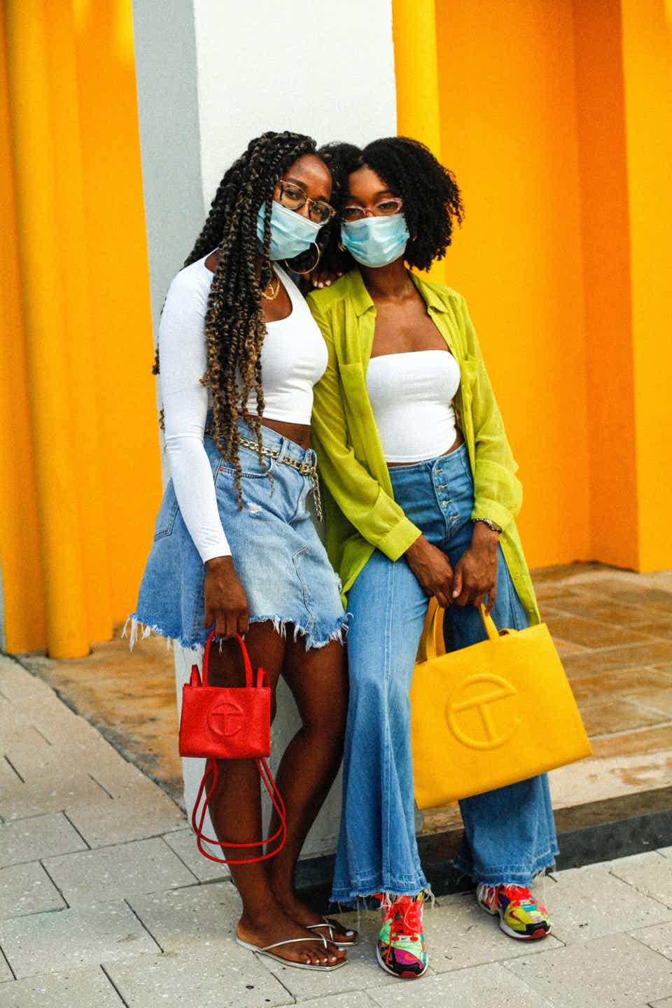 Kristi and Alexandra pose side-by-side with matching Telfar bags, Kristi's a red mini bag and Alexandra's a yellow tote. They're both wearing surgical masks with white tops and jeans.