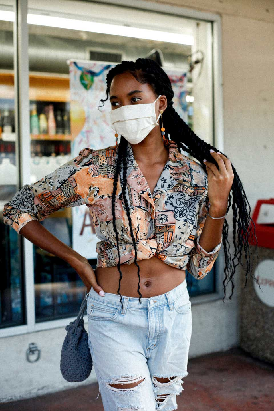 Elidja is wearing a cropped, printed three-quarter sleeve blouse with ripped, light-wash jeans. She's posing, holding her long braids, and wearing a white face mask.