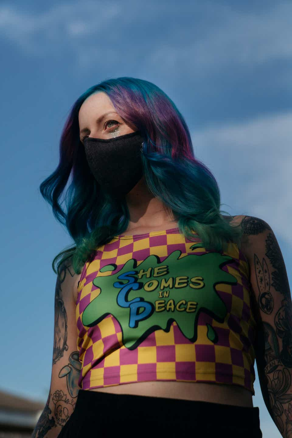 """This is a close-up image of Maddie, who is wearing a pink-and-yellow patterned crop top that says """"She comes in peace"""" on it in yellow and blue font on a green background. She has on a black mask and her hair is colored teal and purple."""